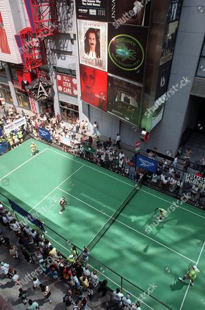 Serena Williams and Luke Jensen, left, play a match against Venus Williams and Murphy Jensen in New York's Times Square, Sunday, Aug. 24, 1997. Courts were laid out for the exhibition matches on the city block as a preface to the the U.S. Open, scheduled to begin on Monday