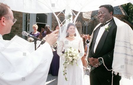 "Stock Image of YAPHET KOTTO Rabbi Joel Braude, left, makes a toast during the wedding ceremony for actor Yaphet Kotto, right, and his bride Tessie Sinahon in Baltimore, Md., Sunday, July, 12, 1998. Kotto plays the imposing Lt. Al Giardello pn NBC's police drama ""Homicide: Life on the Street"