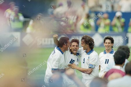 Italian soccer player Roberto Baggio (10) jubilates with teammates after scoring the first of his two goals, tying the game for Italy in their second round World Cup soccer match against Nigeria, at Foxboro Stadium in Foxboro, Mass. Italy defeated Nigeria 2-1 to advance to the quarterfinals against Spain Saturday, July 9 at Foxboro. Joining in are Mauro Tassotti, left, and Paolo Maldini (5