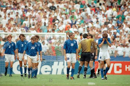 Members of the Italian soccer team leave the pitch at the end of their Group E World Cup soccer match against Mexico which ended in a 1-1 draw at the RFK Stadium on in Washington, D.C. From left, Paolo Maldini (5), Giuseppe Signori (20), Daniele Massaro (partly hidden), Roberto Donadoni (19) and Alessandro Costacurta (4). Unidentified match officials second from left embrace. With the draw, Italy must wait for the results of other matches to learn whether the team will advance to the next round