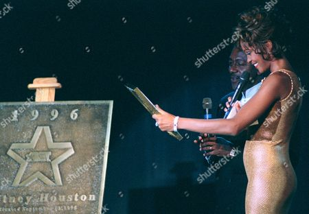 """HOUSTON JOHNSON Singer Whitney Houston admires a small replica of her Walk of Fame Award with Robert L. Johnson, CEO and founder of Black Entertainment Television, Friday night, in Washington. The actual plaque, left, will be placed on the network's """"Walk of Fame,"""" outside of their corporate headquarters in Washington"""