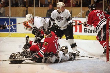 Chicago Blackhawks center Brent Sutter (12) falls on top of Los Angeles Kings goaltender Byron Dafoe (34), while fighting for the puck with Kings Dan Bylsma (42), during early action of the game, at the Pond in Inglewood, Calif. At right, Kings Sean O?Donnell (6) keeps an eye on Blackhawks Bob Probert (24