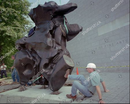 """Stock Photo of WATSON Art installation specialist Peter Watson, of New York City, right, helps install a William de Kooning bronze sculpture called """"Standing Figure"""", (modeled in clay, 1969; cast in bronze, 1984), outside the West Wing entrance of the Museum of Fine Arts in Boston, . The abstract expressionist work of art weighs 7,500 lbs. and measures over 12 feet high and 21 feet wide"""
