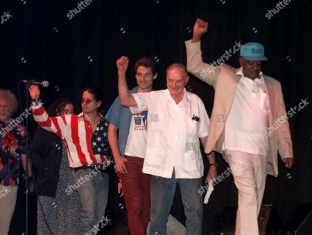 Stock Image of SEALE DELLINGER Bobby Seale, wearing hat, and David Dellinger, behind Seale, lead others onto the stage during a 60's revisited concert in Chicago . The concert was in conjunction with the Democratic National Convention which starts in Chicago Monday, the first Chicago convention since 1968, after which Seale and Dellinger, as part of the Chicago 7, were tried on civil disobedience charges