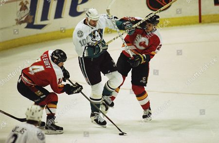 Anaheim Mighty Ducks Roman Oksiuta, center, fights for the puck with the Calgary Flames Theoren Fleury, left, and Cale Hulse during first-period action at the Arrowhead Pond of Anaheim, Calif