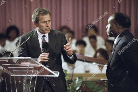 George W. Bush, left, Republican candidate for Texas Governor, turns to Gene Moore, Pastor of the St. Agnes Baptist church, and makes a point during a service address in Houston