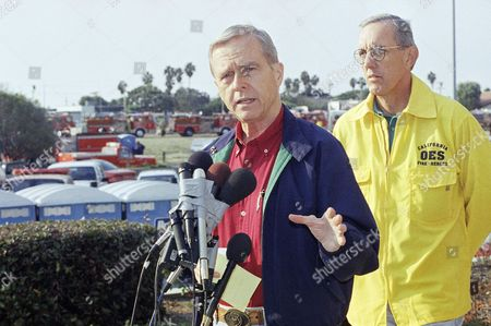 After being briefed by fire chiefs, California Gov. Pete Wilson talks to reporters, accompanied by Richard Evans, director of the Governor?s office of emergency services, at the Malibu, California, civic center on . Wilson praised the efforts of the hundreds of firefighters, combined with Malibu?s stringent brush clearance measures after 1993?s disastrous firestorm that has so far kept the toll of the Calabasas fire much lower than 1993. The fire base camp is in the background