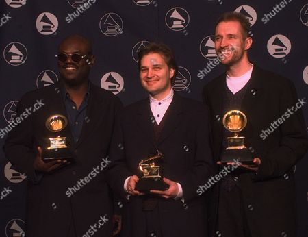 """YEAR Songwriters Tommy Sims, left, Wayne Kirkpatrick, center, and Gordon Kennedy hold up their awards for Song of the Year during the 39th Annual Grammy Awards in New York . They won for their work in """"Change the World"""
