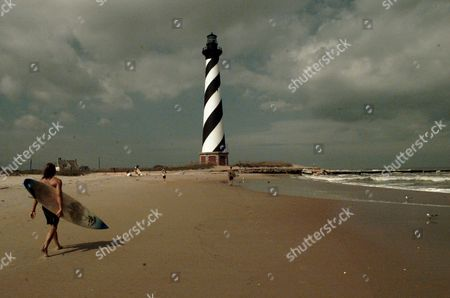 BEACH A surfer carries his board along a deserted beach near the Cape Hatteras lighthouse in Buxton, N.C. Thursday afternoon . Hurricane Felix was expected to landfall on the Outer Banks of North Carolina Thursday but when the stormed stalled off shore it left the popular vaction spot looking like the off season