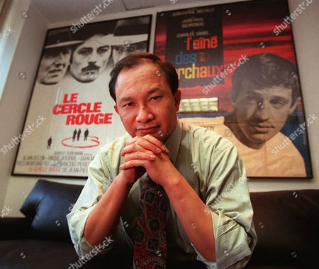 """WOO Film director John Woo, whose latest film is """"Face/Off"""" poses in his Los Angeles office . Behind him are posters for films by French director Jean-Pierre Melville, whom Woo calls his favorite director"""