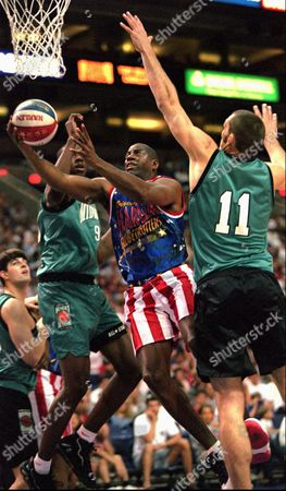 "JOHNSON POLLARD CATO Earvin ""Magic"" Johnson, center, playing for the Harlem Globetrotters, drives past College All-Stars Scot Pollard, of Kansas, (11) and Kelvin Cato, of Iowa State (9) to score during the first half of their World Series of Basketball exhibition game in Phoenix"