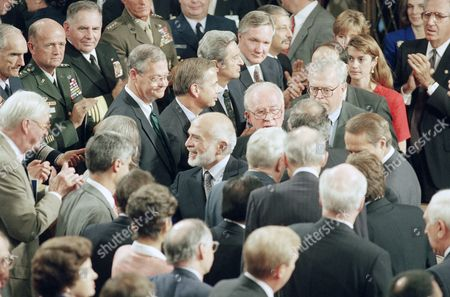 King Hussein of Jordan, center, followed by Israeli Prime Minister Yitzhak Rabin ( to his right) make their way through members of Congress on the floor of the House chamber after their addresses before a joint meeting of Congress in Washington on . Sen. Daniel Patrick Moynihan, D-N.Y., left, and Gen. Gordon Sullivan of the Joint Chiefs of Staff, upper left, look on