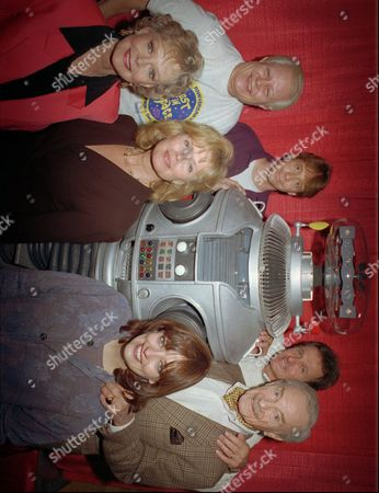 """CAST Crew from the original cast of the television series """"Lost in Space"""" pose for a group portrait with the shows' robot in Boston . The cast, who greeted fans and signed autographs, were reunited for the 30th anniversary of the premiere of the show. From left in the back row are: Bob May, Bill Mumy, Mark Goddard, Jonathan Harris; in the front row from left: June Lockhart, Marta Kristen, Angela Cartwright. Guy Williams, not seen, who played professor John Robinson, died in 1989"""