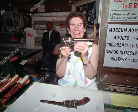 Stock Image of FRANCENA TURILLI 11--Francene Turilli, owner of the Jesse James Museum, holds a pistol, she says Jesse James gave to her husband, Rudy, for taking care of him at the caverns for two years, 1949-1951. The pistol she is holding is a .44 Remington and the pistol on the counter is a .44 Colt that she says once belonged to Frank James, Jesse's brother. Published reports in newspapers like the June 7, 1949, edition of the St. Louis Globe Democrat, the May 19, 1948, edition of The Lawton (Okla.) Constitution, and the Police Gazette all indicate that Jesse James lived a double life and died after living more than one hundred years. However, a recent exhumation of James' grave in Kearney, Mo., indicated he died in 1882 when he was shot and killed by a gang member turned traitor