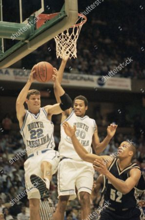 Stock Photo of North Carolina's Pearce Landry (22) handles the ball under the basket as teammate Rasheed Wallace (30) and Georgetown's Don Reid (52) look on during first half NCAA Southeast Regionals play on at the Birmingham-Jefferson Civic Center in Birmingham, Ala