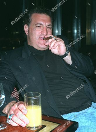 BUTTAFUOCO Joey Buttafuoco puffs a cigar during a visit to a New York restaurant . Buttafuoco, 40, who gained national attention when his then-underage lover, Amy Fisher, shot his wife, Mary Jo, in the head in front of the Buttafuoco's Long Island home in 1992, says he's moving to the West Coast to concentrate on his burgeoning movie career