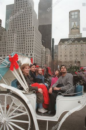"Stock Picture of CORONADO 27--Lisa and Troy Coronado, left, of Washington, D.C., take their family for a carriage ride in New York . Despite the pot-holed streets, thick grime, deafening traffic and rude crowds in America's most populous city, many New Yorkers seem to be on a high. After decades of increasing crime, deteriorating subways and rampant pessimism, things have started getting better in what Newsweek magazine recently called ""The Greatest Metropolis on Earth"