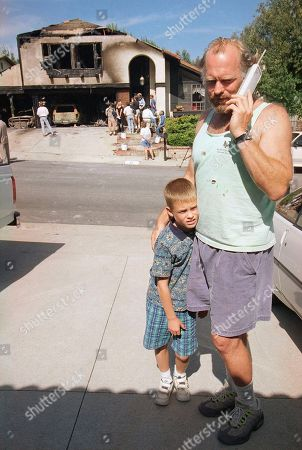 "Stock Picture of Actor Casey Sander, of ABC's ""Grace Under Fire,"" with his son Max Sander, 7, talks in front of the fire-damaged home of his neighbor Scott Miller in Newbury Parks, California, . Sander injured his hand when he tried to help. Miller, the Los Angeles city firefighter who was shot during the 1992 Los Angeles riots, had moved to Newbury Park after the Jan. 17, 1994, earthquake damage"