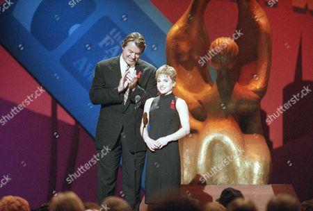 Robert Urich, Kerri Strug Actor Robert Urich applauds as Olympic Gold Medalist Kerri Strug jokes during the Family Film Awards at CBS Studios, in Los Angeles