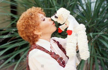 Stock Picture of Entertainer Shari Lewis's poses with Lamb Chop outside her house, in Beverly Hills, California