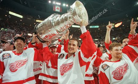 TAYLOR YZERMAN BROWN Detroit Red Wings', from left, Tim Taylor, Steve Yzerman and Doug Brown celebrate with the Stanley Cup after beating the Philadelphia Flyers 2-1 at Joe Louis Arena in Detroit on . Detroit swept the best-of-7 Stanley Cup final series against the Flyers, giving the franchise its first championship since 1955