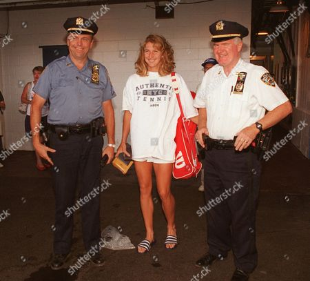 GRAF Germany's Steffi Graf is flanked by two members of New York City's Finest, Sgt. George Innes, left, and Capt. Michael Doherty, as she leaves the National Tennis Center in New York folowing a practice session . Graf will face Argentina's Gabriela Sabatini Friday in the women's semi-final round
