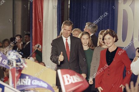 George W. Bush signals to supporters with daughters Jenna, second from left, Barbara from left, and wife Laura, right, in Austin, Texas. Bush beat Democrat Ann Richards