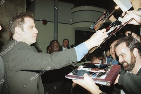 John Travolta, left, signs autographs for fans at the premiere of ?Michael,? in Beverly Hills, Calif. The film stars Travolta along with William Hurt, Robert Pastorelli, Jean Stapleton, and Teri Garr