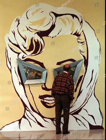 """MURAL A museum viewer gets an up close look at photos set in the eyes of a mural of Marilyn Monroe at the reopening of the Museum of Contemporary Art, San Diego in the La Jolla district of San Diego . The work of art by artist Alexis Smith is titled """"Men Seldom Make Passes At Girls Who Wear Glasses"""