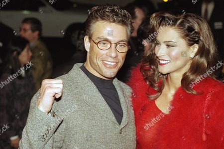 """Actor Jean-Claude Van Damme raises his fist in celebration while arriving with his wife Darcy LaPier at the premiere of his latest movie, """"Sudden Death"""" in Los Angeles on"""