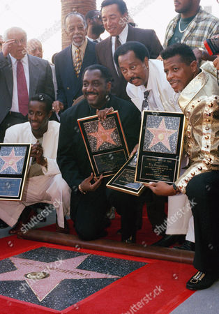 Stock Image of The Temptations, from left to right, Theo Peoples, Otis Williams, Melvin Franklin, and Ali-Ollie Woodson, were given a star on the Hollywood Walk of Fame, in the Hollywood area of Los Angeles. Band member Ron Tyson not able to come to the ceremonies. Smokey Robinson, center rear, looks on