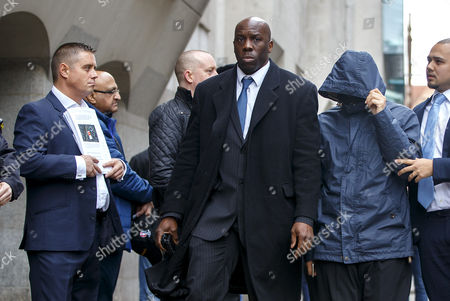 Mazher Mahmood (hooded top) walks past former actor John Alford (far left) as he arrives at The Central Criminal Court