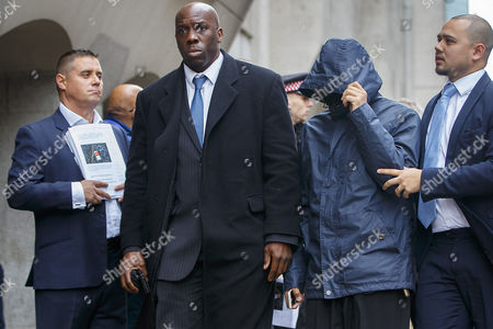 Stock Photo of Mazher Mahmood (hooded top) walks past former actor John Alford (far left) as he arrives at The Central Criminal Court