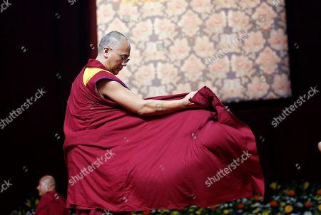 The Dalai Lama Tenzin Gyatso adjusts his robe during a meeting at Milan's Rho Fair, Italy, . The Dalai Lama received honorary citizenship from the city of Milan