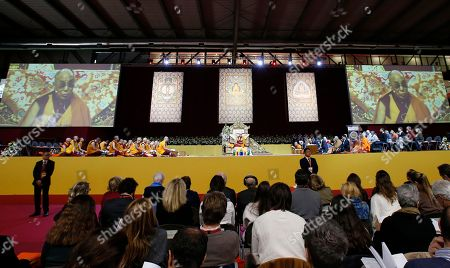 People attend a meeting with the Dalai Lama Tenzin Gyatso, on stage, at Milan's Rho Fair, Italy, . The Dalai Lama received honorary citizenship from the city of Milan