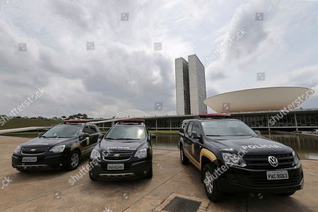 Legislative police cars sit parked outside Congress during a raid by the federal police that's part of the investigation into the Car Wash operation in Brasilia, Brazil, . Police say they have arrested four legislative police agents posted in the Senate for allegedly obstructing an investigation into the suspected involvement of lawmakers in the corruption-kickback scheme at state owned oil company Petrobras. Among those arrested was the head of the Senate police, Pedro Carvalho, according to authorities