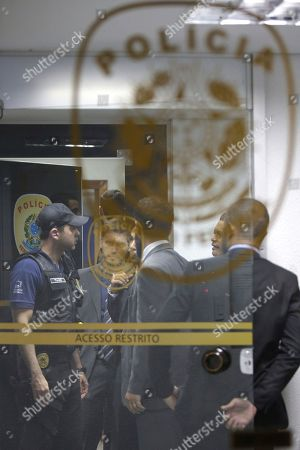 A federal police officer, left, stands with Legislative Police agents, wearing suits, during a federal police raid at the Senate police headquarters as part of the investigation into the Car Wash operation in Brasilia, Brazil, . Police say they have arrested four legislative police agents posted in the Senate for allegedly obstructing an investigation into the suspected involvement of lawmakers in the corruption-kickback scheme at state owned oil company Petrobras. Among those arrested was the head of the Senate police, Pedro Carvalho, according to authorities