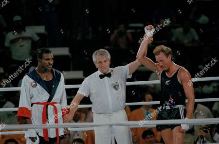 Evander Holyfield, Kevin Barry, Gligorije Novicic Yugoslavian referee Gligorije Novicic, center, raises the hand of boxer Kevin Barry of New Zealand as a dejected Evander Holyfield of Atlanta, Ga., looks, at the Summer Olympics in Los Angeles, Calif., . Holyfield had earlier knocked Barry through the ropes, and had the fight well in hand until Novicic disqualified him at the end of the second round for hitting on the break