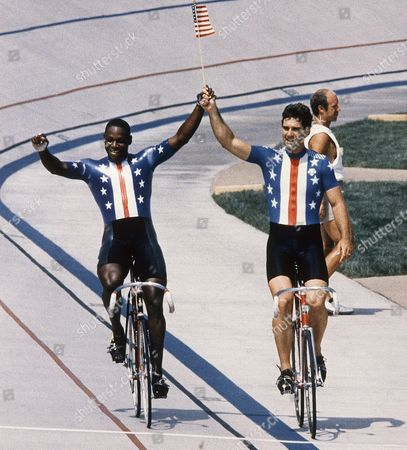 Stock Photo of United States Cyclists Mark Borski, right, of Costa Mesa, Ca., and Nelson Vails of New York, carry an American flag around track at the Olympic cycling venue in Carson, Calif., after the finals in the men's 1,000-meter sprint . Borski edged out Vail to take the gold medal, with Vail winning the silver