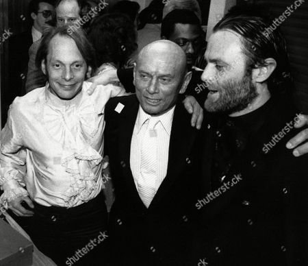 Yul Brynner, Rock Brynner, Isaac Tigrett Actor Yul Brynner, center, poses with son, Rock, Left and Isaac Tigrett at the opening of the Hard Rock Cafe in New York, . Tigrett and actor Dan Aykroyd are co-owners. Rock Brynner is the night manager