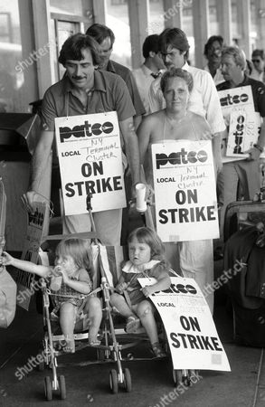 Striking air traffic controller Bill Haney pushes his two daughters Alison and Meghan, 22-months old, on the picket line at La-Guardia airport in New York, . At right is Haney's wife Meredith