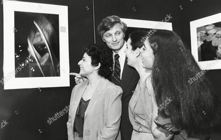 Actor Alan Alda gets a laugh from daughters Beatrice, 19, right, and Elizabeth, 20, while viewing one of Arlene Alda's photos on exhibit at New York's Nikon House Gallery on . Mrs. Alda, left, an award-winning photo-essayist, will display her color nature close-ups and black and white portraits from a motion picture set at the gallery through Saturday
