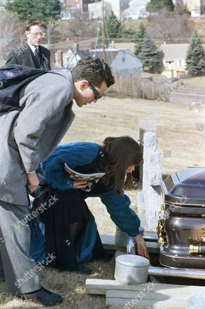 Interview Magazine staff member Paige Powell drops a copy of the publication into the grave of pop artist Andy Warhol during funeral services for Warhol at St. John the Baptist Byzantine Catholic Cemetery in Bethel Park, Pennsylvania on . Warhol, who was the founder of the magazine, died on Sunday in New York