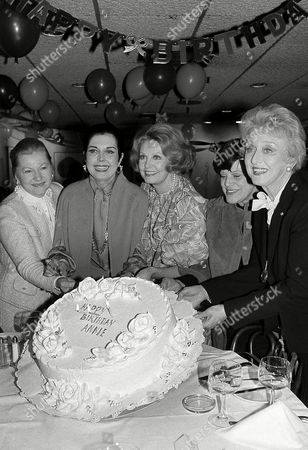 """Ann Miller Ann Miller, second from left, star of """"Sugar Babies,"""" holds up a birthday cake during a party marking her 59th birthday at Bruno's restaurant in New York on . Joining the celebration, from left, are: Joan Fontaine, Miller, Arlene Dahl, Kay Ballard and Celeste Holm"""