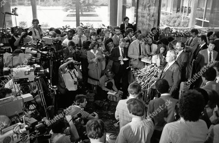 Israeli Defense Minister Ariel Sharon, right, behind microphones, talks with a mass of reporters and photographers gathered in the State Department lobby in Washington on . Sharon met with Secretary of State George Shultz in his continuing sessions on Friday with senior officials of the Reagan Administration