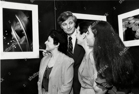 ALDA FAMILY Actor Alan Alda gets a laugh from daughters Beatrice, 19, right, and Elizabeth, 20, while viewing one of his wife Arlene Alda's photos on exhibit at New York's Nikon House Gallery . Mrs. Alda, left, an award-winning photo-essayist, was to display her color nature close-ups and black and white portraits from a motion picture set at the gallery