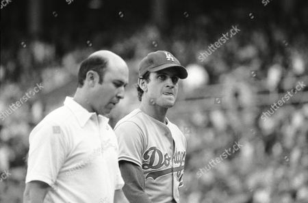 Los Angeles Dodgers pitcher Bob Welch bites his tongue as he is escorted from the field by trainer Paul Padilla after being taken out of the game in second inning of a League Championship game against the Philadelphia Phillies in Philadelphia on
