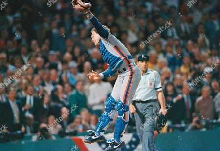 New York Mets catcher Gary Carter lunges in the air to field the late throw to the plate as Boston Red Sox Bill Buckner scored the second run of the game on a single by Dwight Evans in the third inning of the fifth game of the World Series at Boston's Fenway Park, on Thursday night