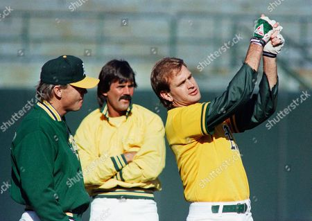 Oakland A's pitcher Bob Welch demonstrates a swing for teammate Dennis Eckersley, center, and pitching coach Dave Duncan during Thursday's World Series workout in the Oakland coliseum. Athletics tangle with cross-bay rivals, the San Francisco Giant in first game on