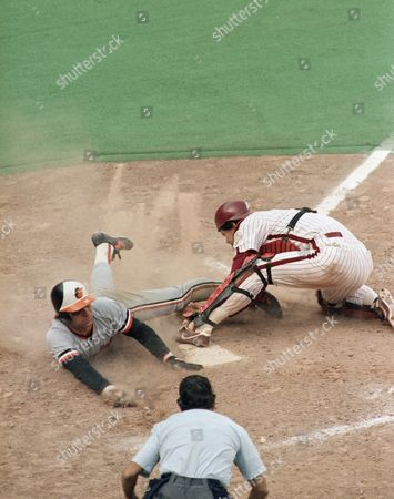 Baltimore Orioles Jim Dwyer, left, slides home safely past the tag by Philadelphia Phillies catcher Bo Diaz, right, as home plate umpire Frank Pulli, center, watches in the seventh inning of the World Series, Philadelphia, Pa. Dwyer scored on a hit by Rich Dauer